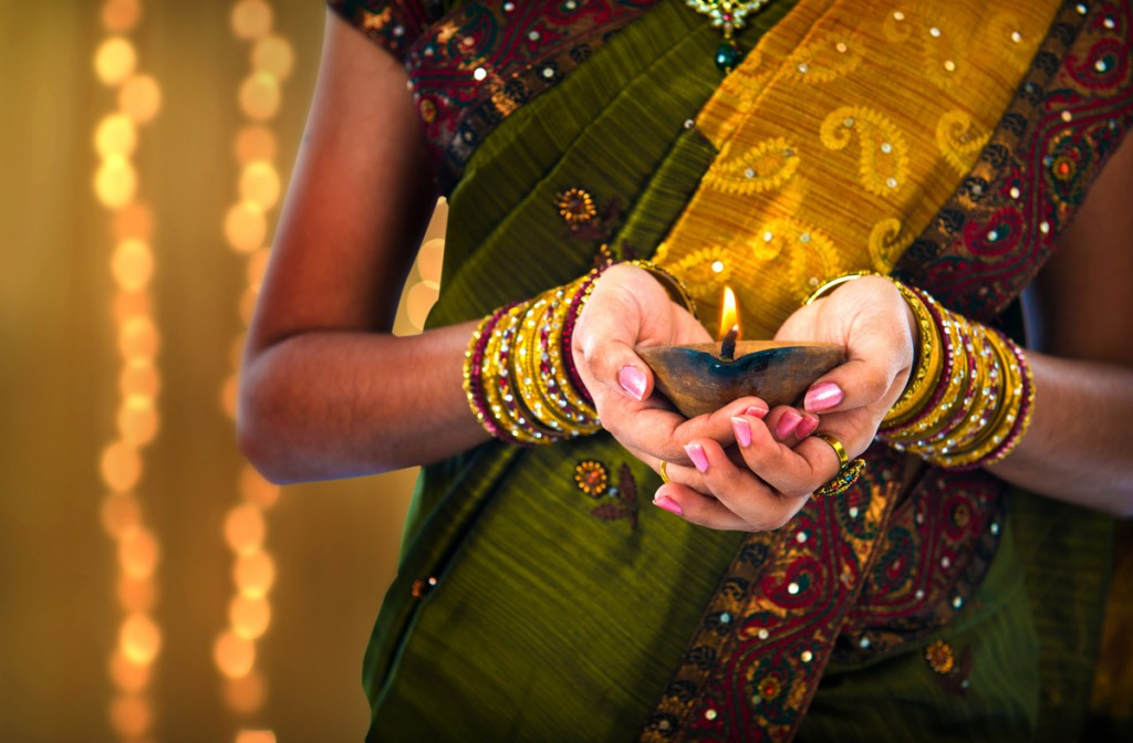 Female holding oil lamp during Diwali | Photo Credit: Shutterstock